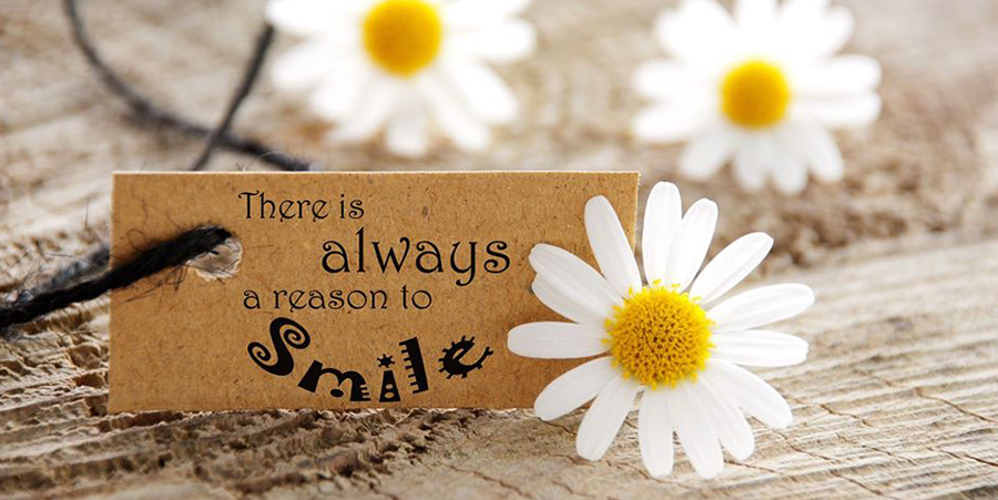 There is always a reason to smile - flowers and tag on a wooden table